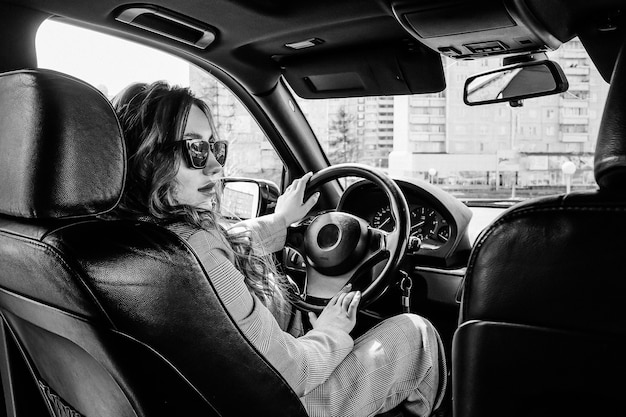 Young, beautiful girl driving a car. a stylish girl in a suit and glasses driving a black car. black and white photo
