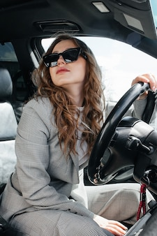 Young, beautiful girl driving a car. a stylish girl in a suit and glasses driving a black car.