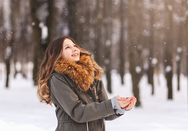 젊은 아름 다운 소녀는 공원에서 화창한 날에 눈을 즐깁니다.