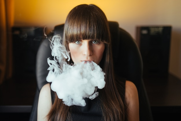 Young beautiful girl exhaling smoke from a hookah and looking at the camera