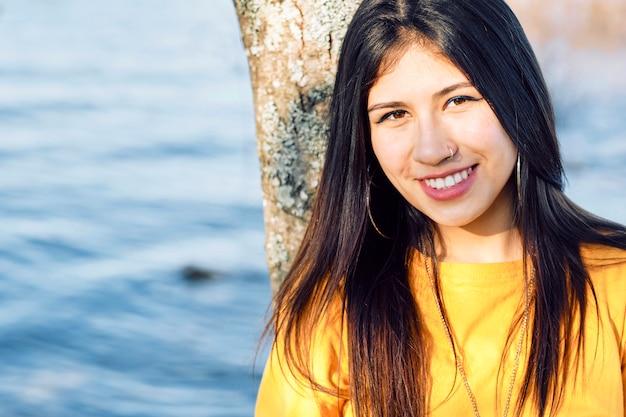 Молодая красивая девушка лицо с черными и длинными волосами в естественном пространстве