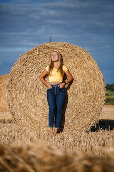 A young beautiful girl in a field stands near a sheaf. vacation in the village. young woman in yellow top and jeans