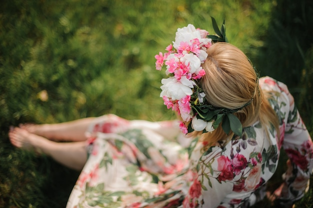 Young and beautiful girl in a flower diadem sitting on the grass