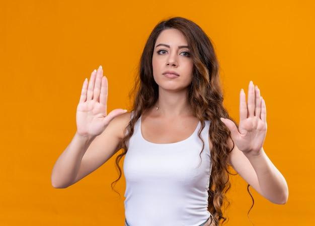 Giovane bella ragazza che gesturing no sulla parete arancione isolata