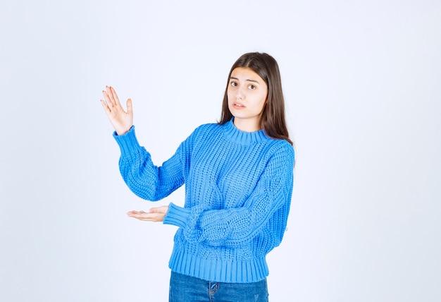 大きなサイズと大きなサイズのサインを示す手で身振りで示す若い美しい少女。