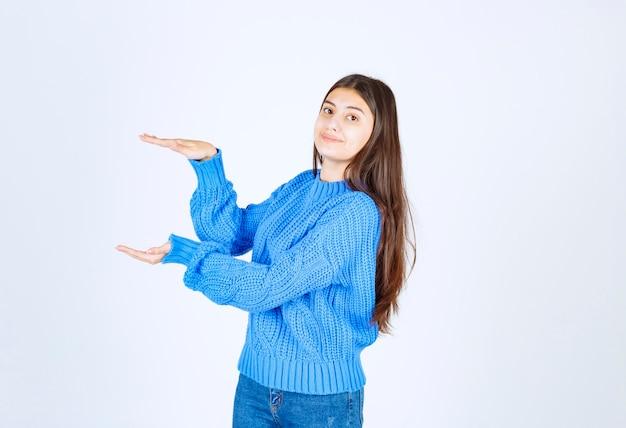 Giovane bella ragazza che gesturing con le mani che mostrano il segno di grandi e grandi dimensioni.