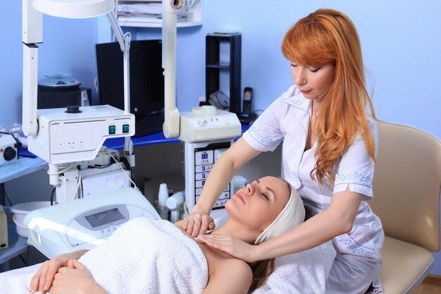 スパトリートメントを受ける若い美しい少女。顔のマッサージをしている医者。
