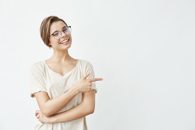 Young beautiful girl in glasses smiling winking pointing finger in side .