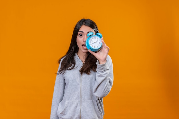 Young beautiful girl in gray holding clock and looking at camera surprise on face standing over orange background