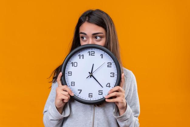 Giovane bella ragazza in felpa con cappuccio grigia che tiene l'orologio e distoglie lo sguardo con preoccupazione in piedi su sfondo arancione d