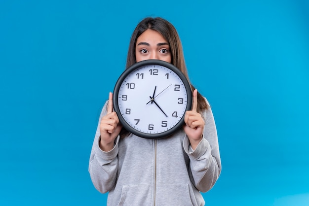 Young beautiful girl in gray hoody holding clock and looking at camera with surprised sight standing over blue background