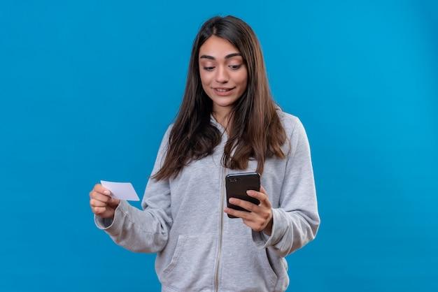 Giovane bella ragazza in felpa con cappuccio grigia che tiene telefono e carta guardando la sorpresa del telefono sul viso in piedi su sfondo blu