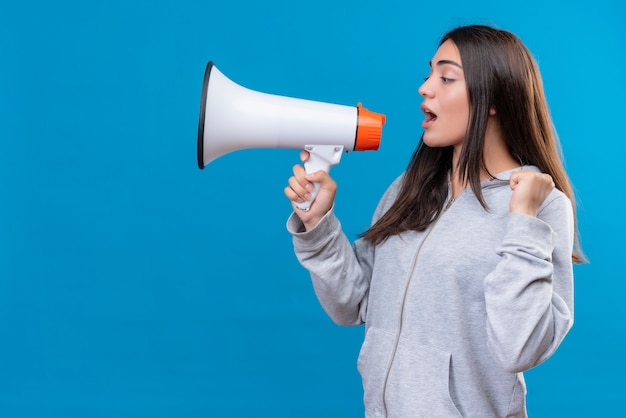 Young beautiful girl in gray hoody looking away and speaking to loudspeaker  standing over blue background