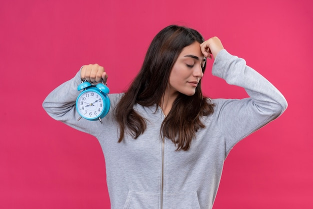 Young beautiful girl in gray hoody looking away with hand on forehead thinking holding clock standing over pink background