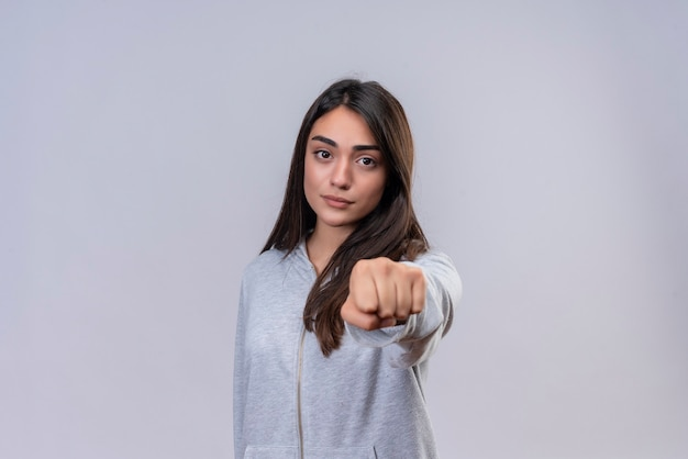 Young beautiful girl in gray hoody looking at camera  clenching fist to camera with angry expression standing over white background
