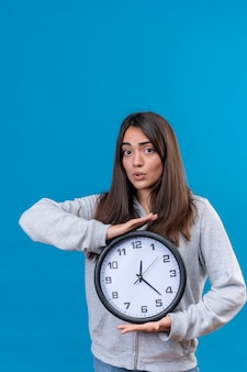 Young beautiful girl in gray hoody looking at camera with shock on face and holding clock standing over blue background