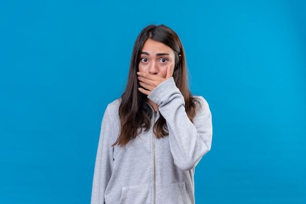Giovane bella ragazza in felpa con cappuccio grigia che guarda l'obbiettivo con shock e mano sulla bocca in piedi su sfondo blu