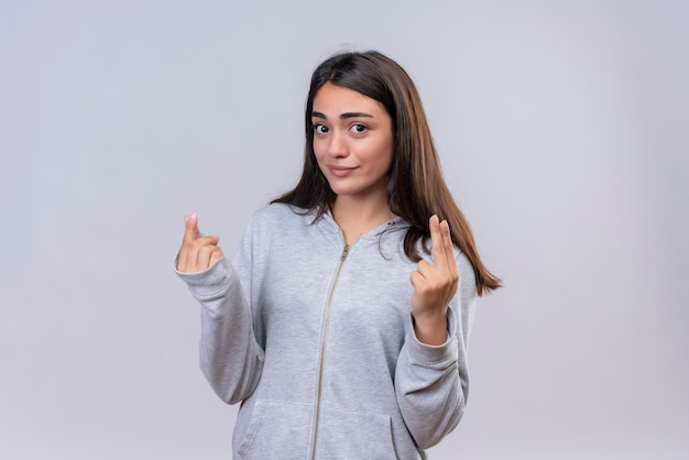 Young beautiful girl in gray hoody looking at camera with smile on face making money gesture standing over white background