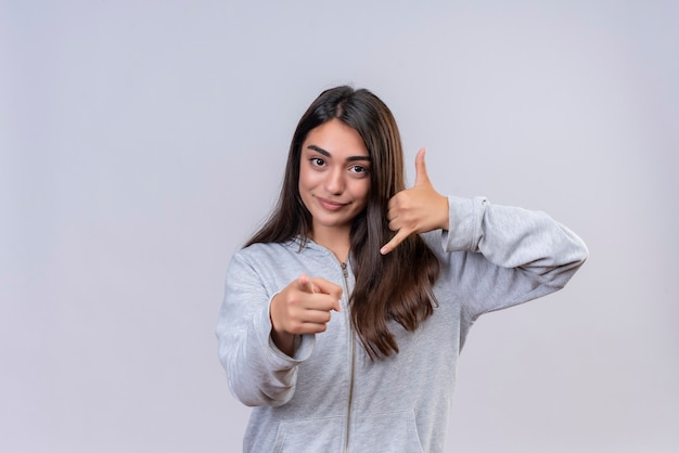 Young beautiful girl in gray hoody looking at camera with smile on face pointing to camera making call me gesture standing over white background
