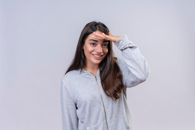 Giovane bella ragazza in felpa con cappuccio grigia che guarda l'obbiettivo con il sorriso sul viso mettendo la mano sulla fronte in piedi su sfondo bianco
