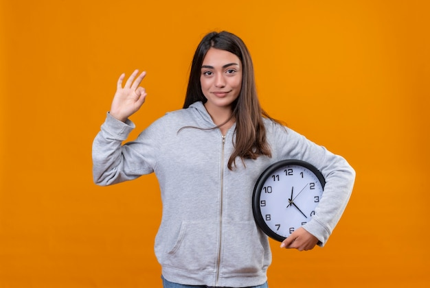 Young beautiful girl in gray hoody making finger like okey gesture and the other hand she takes clock standing over orange background