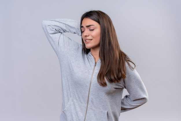 Young beautiful girl in gray hoody with closed eyes touching head for mistake looking confused bad memory concept standing over white background