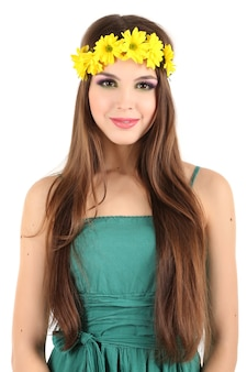 Young beautiful girl in green dress with bright wreath on her head, isolated on white surface