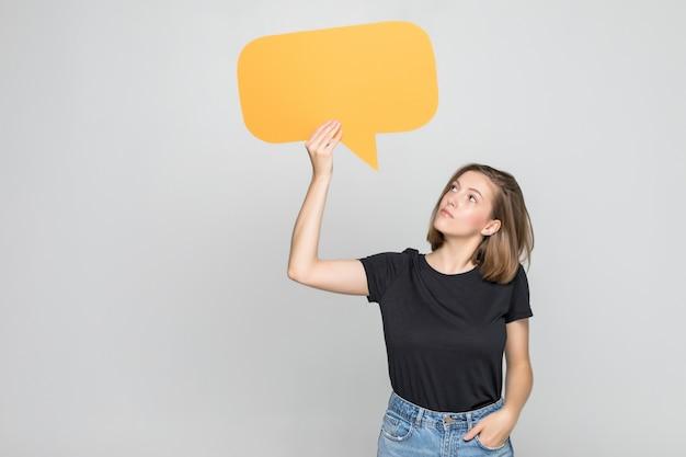 Молодая красивая девушка держит зеленый пузырь для текста, изолированные на белой стене