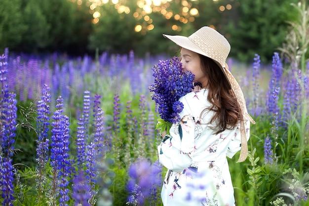 Молодая красивая девушка держит большой цветок с фиолетовым люпином в цветущем поле.