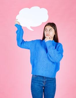 Молодая красивая девушка держит белый пузырь для текста на розовом.
