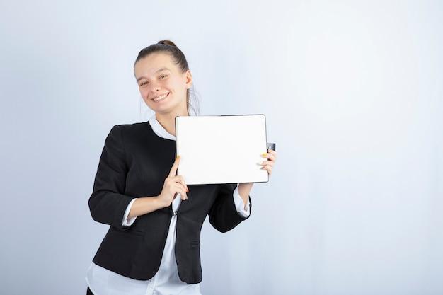 Giovane bella ragazza che tiene libro mentre sorridente su sfondo bianco. foto di alta qualità