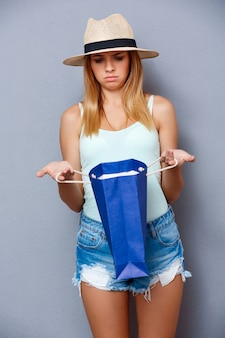 灰色の背景の上にカラフルなバッグを置く美しい少女。