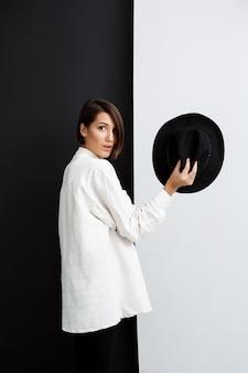 검은 색과 흰색 벽에 모자를 들고 젊은 아름 다운 소녀