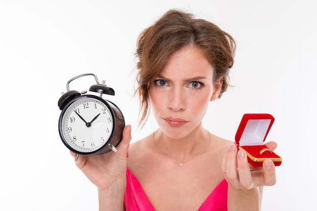 Young beautiful girl holds a box for a engagement ring and alarm clock and is angry