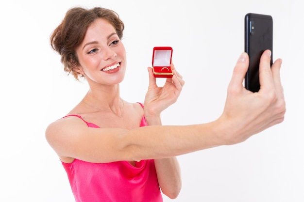 Young beautiful girl holds a box for a engagement ring and do selfie with it isolated on white