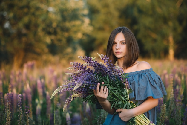 Young beautiful girl holds a large bouquet of purple lupins in a flowering field. summer photo. photo at sunset