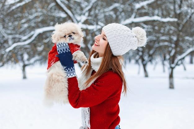 若い美しい少女は彼の手で小さな子犬を保持し、彼と遊んでいます