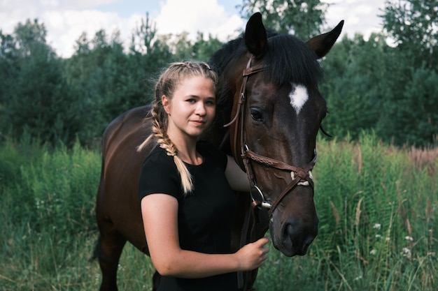自然の中で馬を抱き締める若い美しい少女。馬の恋人。