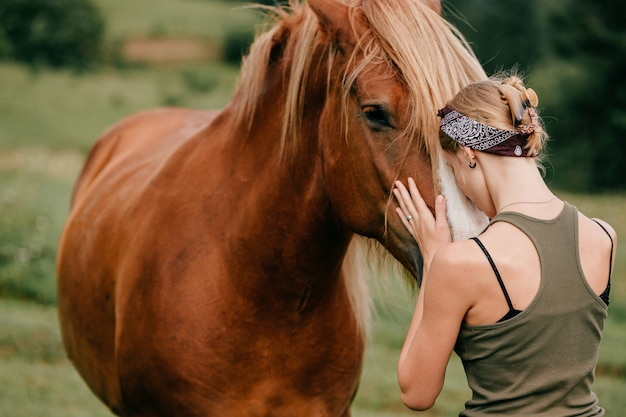 Young beautiful girl hugging horse at nature