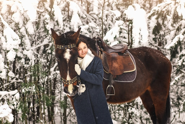 Young beautiful girl hugs a horse in the park in winter