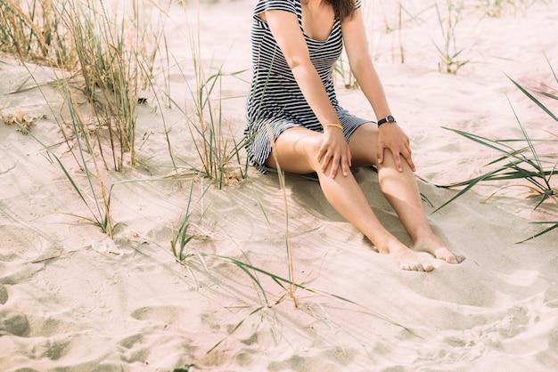 海沿いの芝生の横にある砂の上にビーチドレスの美しい少女が座っています。海で休む。砂に残った足跡。