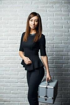 Молодая красивая девушка в черном платье держит стильный алюминиевый корпус на фоне белой кирпичной стены