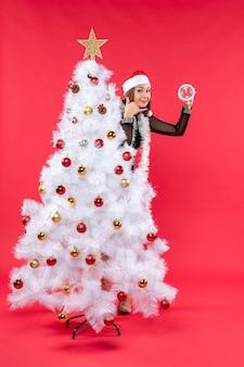 Молодая красивая девушка в черном платье в шляпе санта-клауса прячется за рождественской елкой, держит часы и делает жест `` позвони мне ''