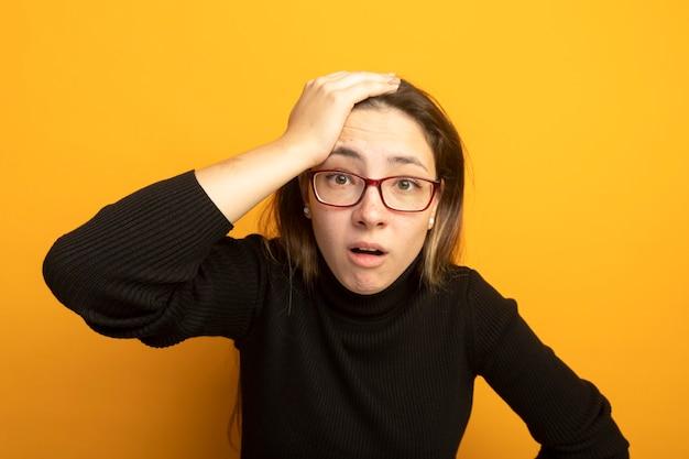 黒いタートルネックと眼鏡をかけた若い美しい少女が混乱し、頭に手を当てて非常に心配しています