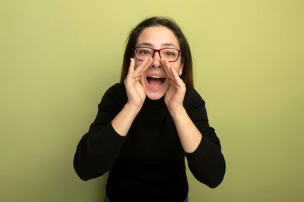 黒いタートルネックとメガネの若い美しい少女は、口の近くの手で幸せで興奮した叫び
