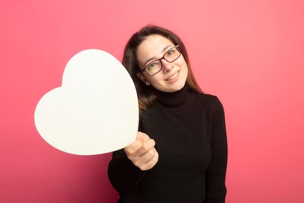 幸せそうな顔で笑顔の段ボールの心を保持している黒いタートルネックとメガネの若い美しい少女