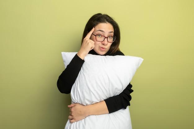 Молодая красивая девушка в черной водолазке и очках держит подушку, указывая указательным пальцем на висок, сосредоточенная на задаче