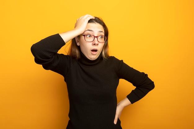 黒いタートルネックと眼鏡をかけた若い美しい少女は、驚いて頭の上の手で混乱しているのを脇に見ています