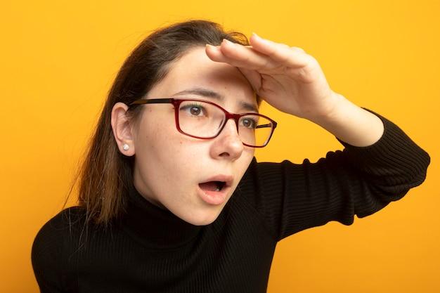 黒いタートルネックと眼鏡をかけて遠くを見ている若い美しい少女
