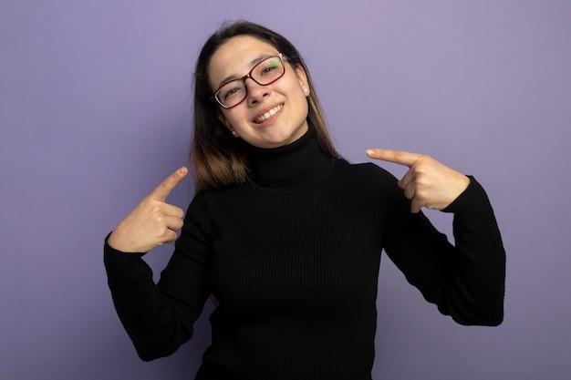 Молодая красивая девушка в черной водолазке и очках, указывая пальцами на себя, счастливая и позитивная Бесплатные Фотографии